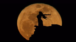 red-moon-rising-women-with-arms-open-wide-silhouette-animation-4k_eolpnlc73l__S0000
